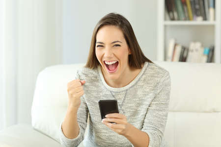 Front view portrait of an excited woman holding phone looking at you sitting on a sofa in the living room of a house interior Фото со стока