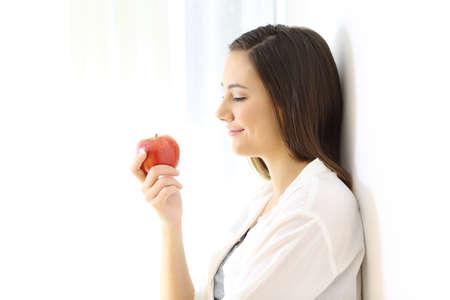 横に白く隔離されたリンゴを見ている女性の側面図