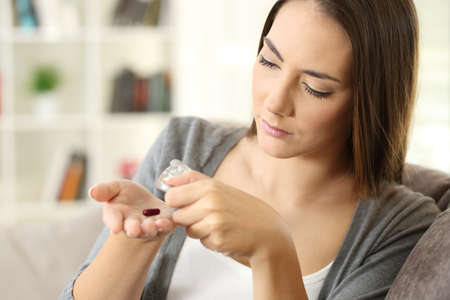 Woman extracting a pill from the blister sitting on a couch at home Stock fotó - 90087842