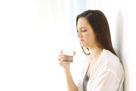 Disgusted woman drinking water with bad taste isolated on white at side