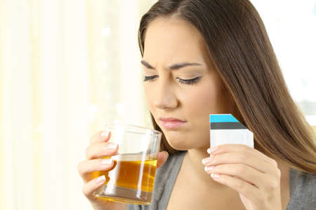 Disgusted woman taking a liquid medicine with bad taste at home
