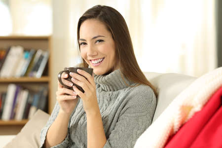 bebes lindos: Portrait of a happy woman posing holding a coffee mug sitting on a sofa in the living room in a house interior in winter
