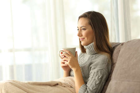 Portrait of a pensive relaxed woman holding a coffee mug sitting on a sofa in the living room of a house interior