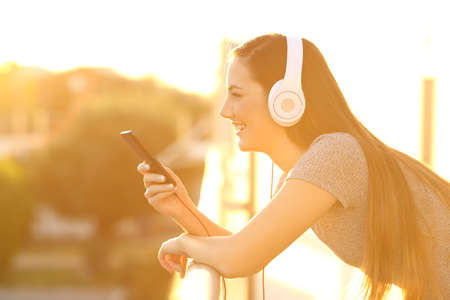 Side view portrait of a happy girl listening music with headphones and smart phone in a house balcony at sunset with an orange light Stock Photo