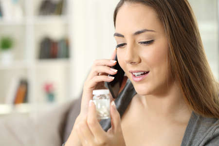 Happy woman calling doctor on phone asking information about bottle of pills sitting on a couch in a house interior