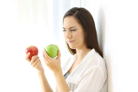 Doubtful woman deciding between red and green apples isolated on white at side Stockfoto