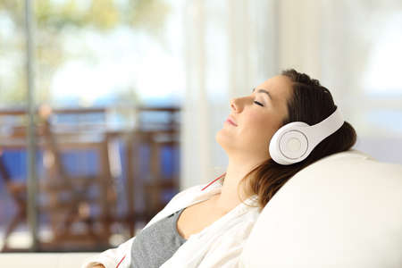 Side view portrait of a woman relaxing listening to music on a couch in the living room at home 免版税图像