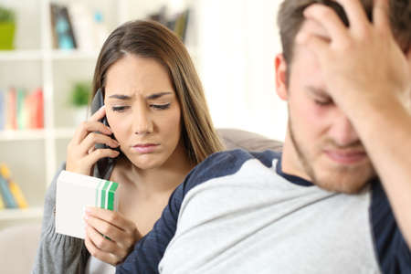 Wife calling doctor on phone to help her ill husband sitting on a couch at home
