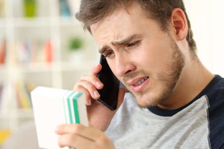 Worried man calling doctor on phone asking about medicines information sitting on a couch at home Stock Photo