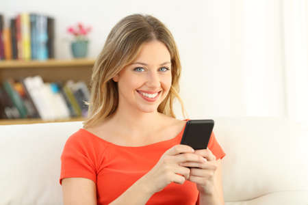 Blonde happy girl looking at camera holding a smart phone sitting on a sofa in the living room at home Standard-Bild