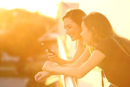 Two happy friends using a smart phone in a house balcony at sunset with an orange light