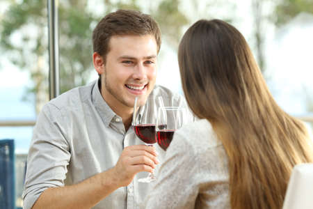 Happy couple dating and drinking wine sitting in a table in a restaurant Stock Photo