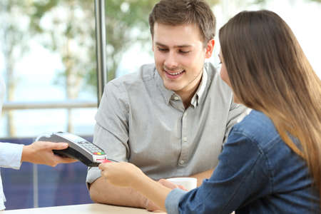 Happy couple paying with credit card in a bar interior