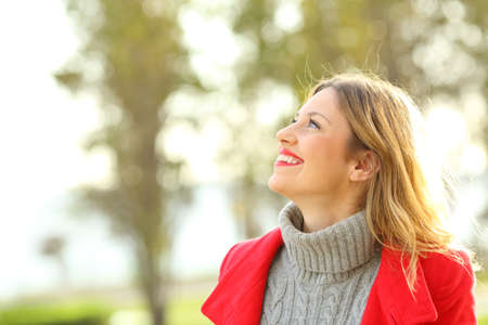 Profile of a happy fashion woman wearing a red jacket looking above in winter