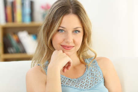 Front view portrait of a woman with blue eyes looking at you sitting on a sofa in the living room in a house interior