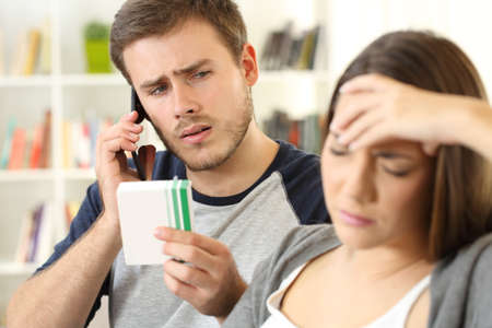 Husband helping his sick wife calling doctor on phone sitting on a couch at home Stock Photo