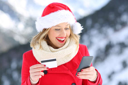 Surprised buyer paying on line with credit card and smart phone in christmas with a snowy mountain in the background