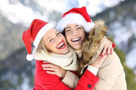 Two happy friends on christmas holidays looking at you with a snowy mountain in the background Stock Photo