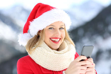 Happy woman looking at you holding phone in christmas with a snowy mountain in the background