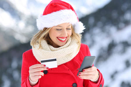 Happy woman wearing santa claus hat paying on line with credit card in christmas with a snowy mountain in the background Stock Photo