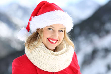 Portrait of a happy woman posing with santa claus hat in christmas holidays with a snowy mountain in the background