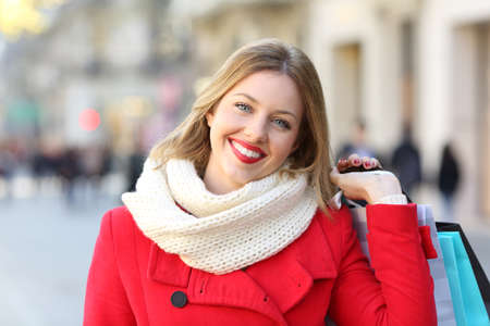 Front view portrait of a happy shopper looking at camera in winter on the street Stock Photo