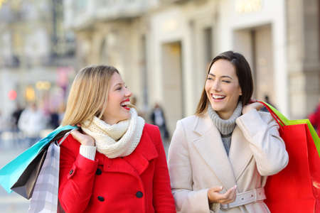 Two happy shoppers talking and walking on the street in winter
