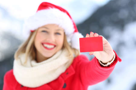 Front view portrait of a woman showing a blank credit card in christmas holidays with a snowy mountain in the background Stock Photo