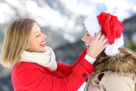 Side view portrait of two friends joking in christmas holidays with a santa claus hat with a snowy mountain in the background
