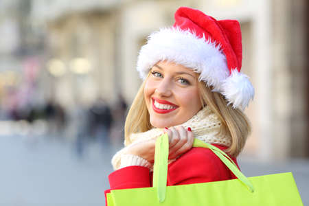 Portrait of a happy girl wearing santa claus hat shopping in christmas looking at you outdoors on the street Stock Photo