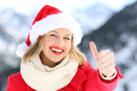 Front view portrait of a woman wearing santa claus hat on christmas holidays with thumbs up with a snowy mountain in the background Banco de Imagens