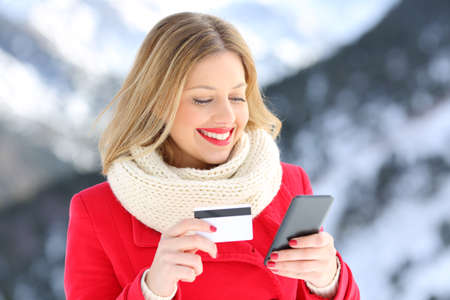 Portrait of a smiley woman paying with credit card and mobile phone in winter with a snowy mountain in the background