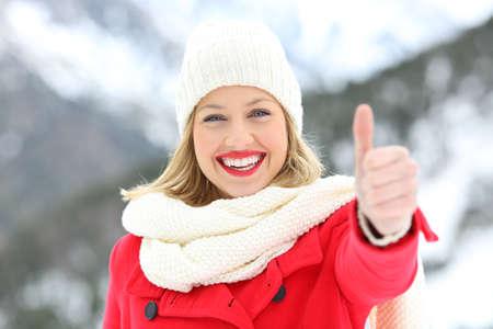 Vorderansicht Porträt einer Frau in rot mit Daumen hoch im Winter mit einem schneebedeckten Berg im Hintergrund