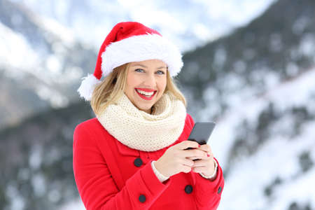 Portrait of a happy woman on christmas holidays using phone looking at you with a snowy mountain in the background