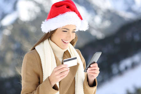 Portrait of a woman wearing santa claus hat on christmas paying on line with credit card and smart phone with a snowy mountain in the background