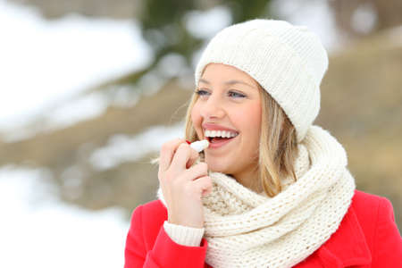 Meisje die lippen met lippenbalsem in de winter met een sneeuwberg op de achtergrond beschermen Stockfoto