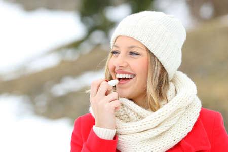 Schützende Lippen des Mädchens mit Lippenbalsam im Winter mit einem schneebedeckten Berg im Hintergrund
