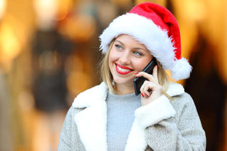 Happy woman wearing santa claus hat calling on mobile phone in christmas on the street in a commercial centre