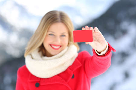 Front view portrait of a woman showing a credit card in winter with a snowy mountain in the background