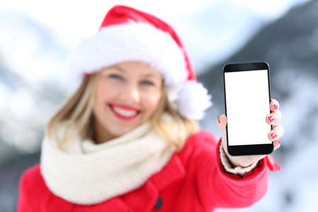 Girl on christmas holidays showing phone screen with a snowy mountain in the background