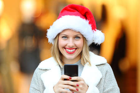 Front view portrait of a beautiful woman wearing santa claus hat on christmas holidays holding smart phone on the street