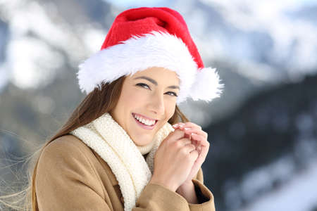Smiley woman on christmas holidays looking at you with a snowy mountain in the background Stock Photo
