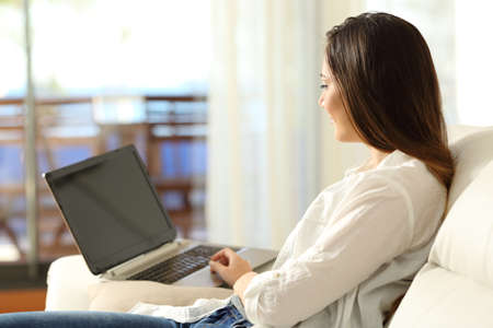 Serious woman using a laptop sitting on a sofa in the living room in an apartment interior