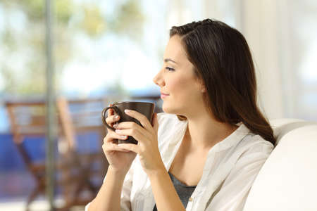 Zijaanzichtportret van een ernstige peinzende vrouw die houdend een koffiemok ontspannen die weg zittend op een bank in de woonkamer in een huisbinnenland kijken Stockfoto - 91196314