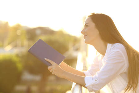 Side view portrait of a happy woman dreaming reading a paper book outdoors in a balcony at sunset with a warm light in the background Stock Photo