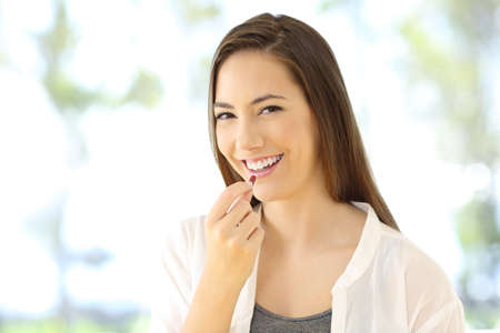 Portrait of a smiley woman taking a pill looking at you Stock Photo