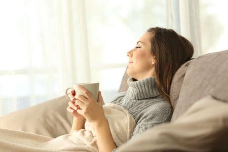 Porträt eines entspannenden Sitzens der nachdenklichen Frau auf einem Sofa im Wohnzimmer in einem Hausinnenraum im Winter Standard-Bild