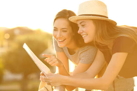 Two funny tourists reading a paper map in an hotel balcony on holidays at sunset Stock Photo