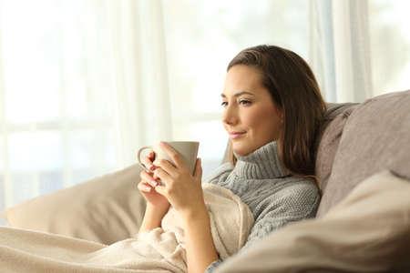 zrelaksowany najemca odpoczywa trzymając kubek kawy siedząc na kanapie w salonie we wnętrzu domu