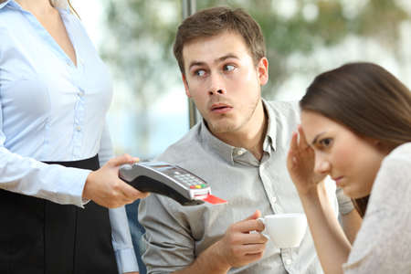 Disloyal boyfriend looking at waiter chest in front of his embarrassed girlfriend
